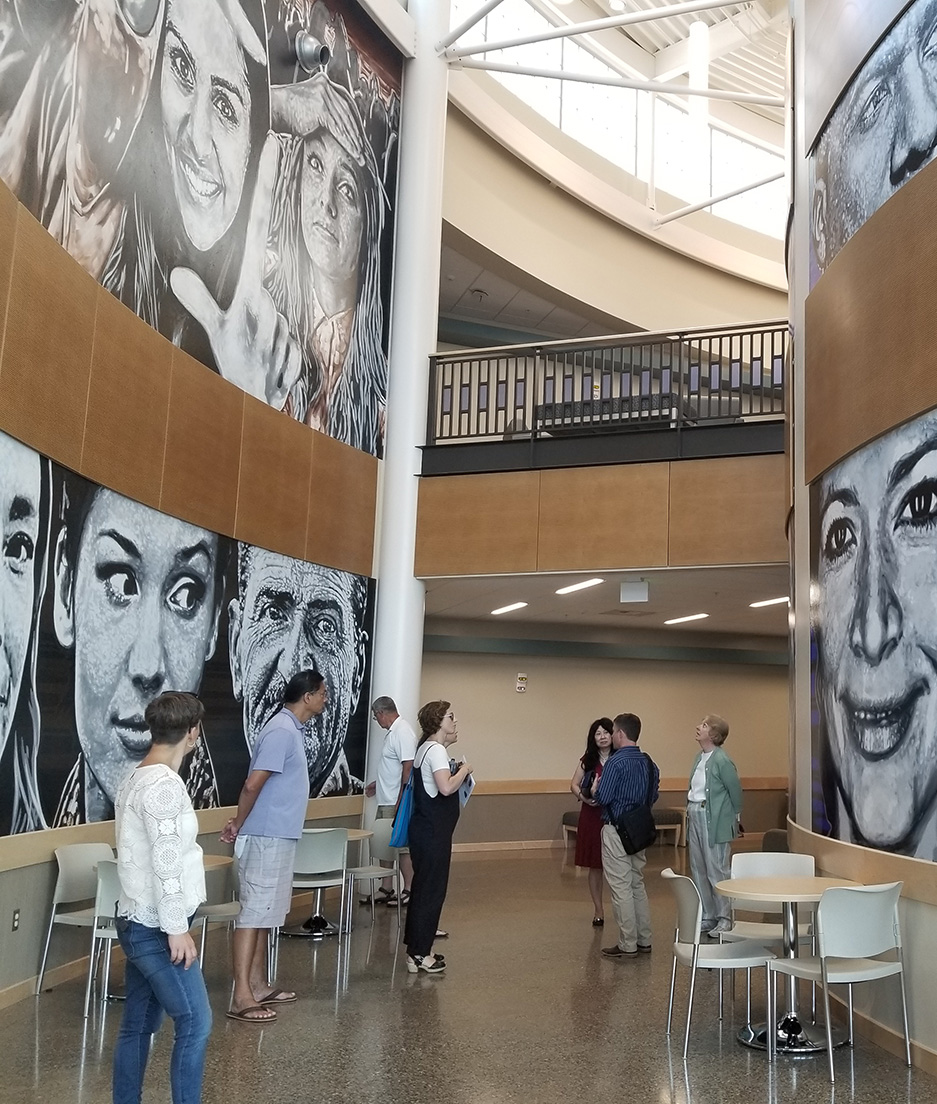 """AIPP staff leading an ArtsWA Board tour of Todd Benson's multi-part mural """"Infinite Humanity"""" (2017), located in the Social Studies and World Languages Building at Columbia Basin College, Pasco. Photo by ArtsWA. This artwork is part of Washington's State Art Collection."""