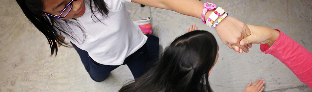 Three girls play a game. Two of the girls are holding hands up high like a bridge and the third girl is about to pass under them.