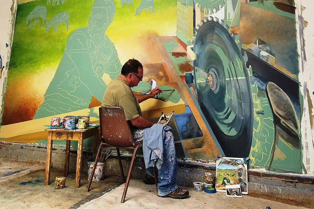 "Artist Daniel Galvez at work on his five-part mural ""Legacy"" (2017), located at White Pass High School, Randle. Photo courtesy of the artist. Part of Washington's State Art Collection."