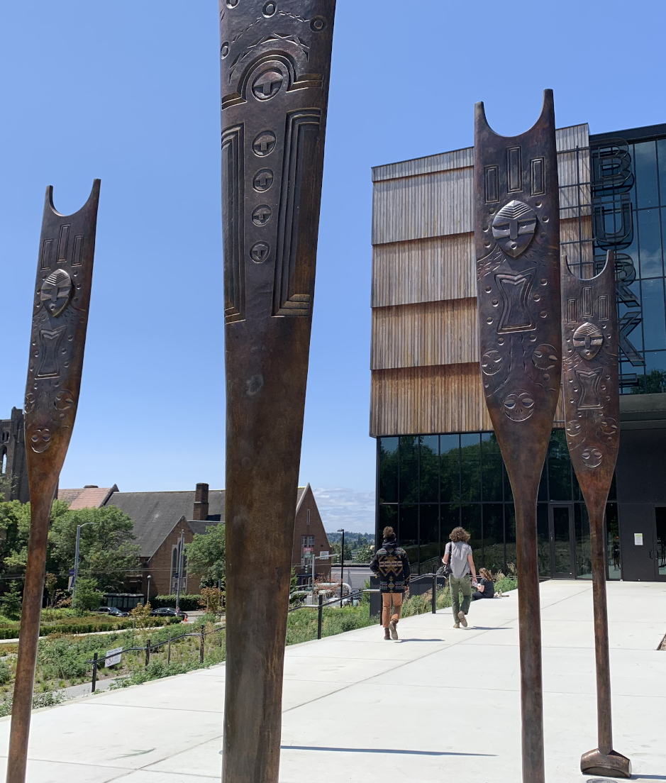 Outdoor artwork of upright, carved, bronze paddle at the Burke Museum in Seattle.
