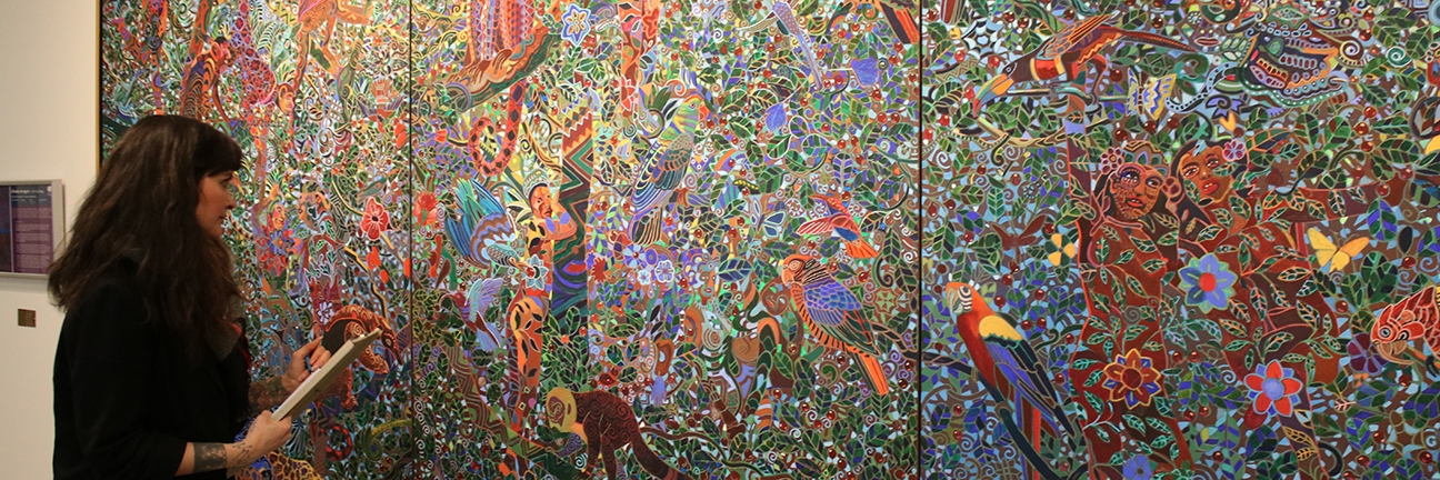 A woman is carefully looking at and evaluating the condition of a highly-patterned painting of a jungle.